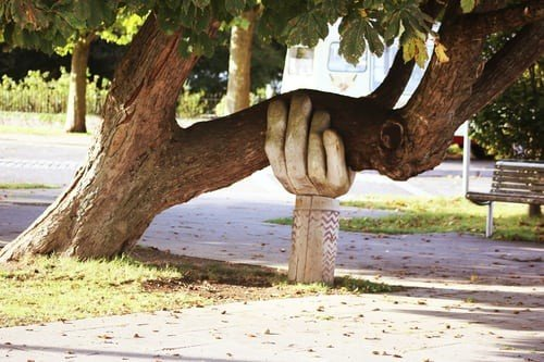 Carved wooden Hand holding up a Tree